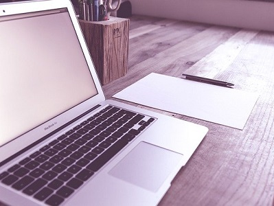 Laptop, daneben Blatt mit Stift