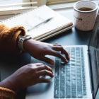 Frau vor Laptop mit Notizbuch und Kaffee