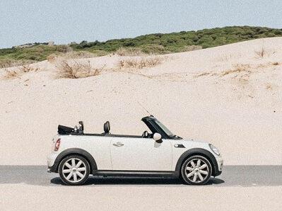 weißes Mini Cabrio vor einer Sanddüne