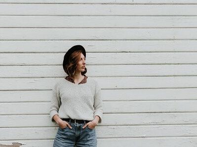 Frau mit Hut vor weißer Holzwand